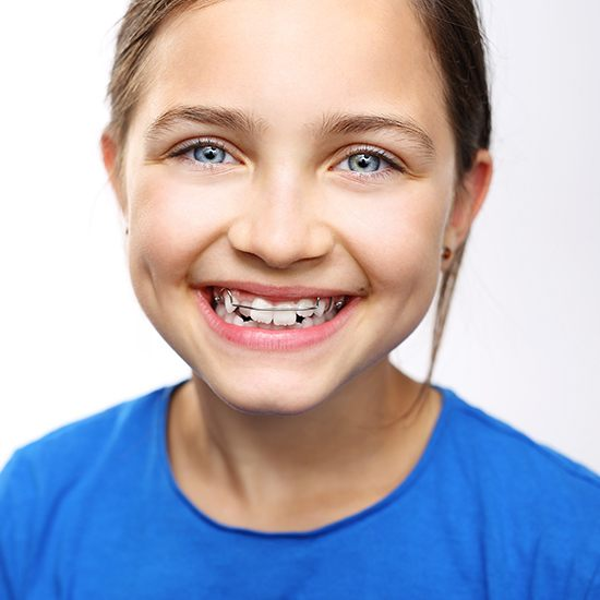 Young girl with orthodontic appliance smiling