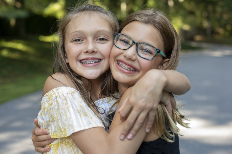 Two girls hugging and smiling with braces