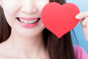 Woman with adult braces in Hudson holding paper heart and smiling