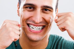 Closeup of smiling man flossing with braces