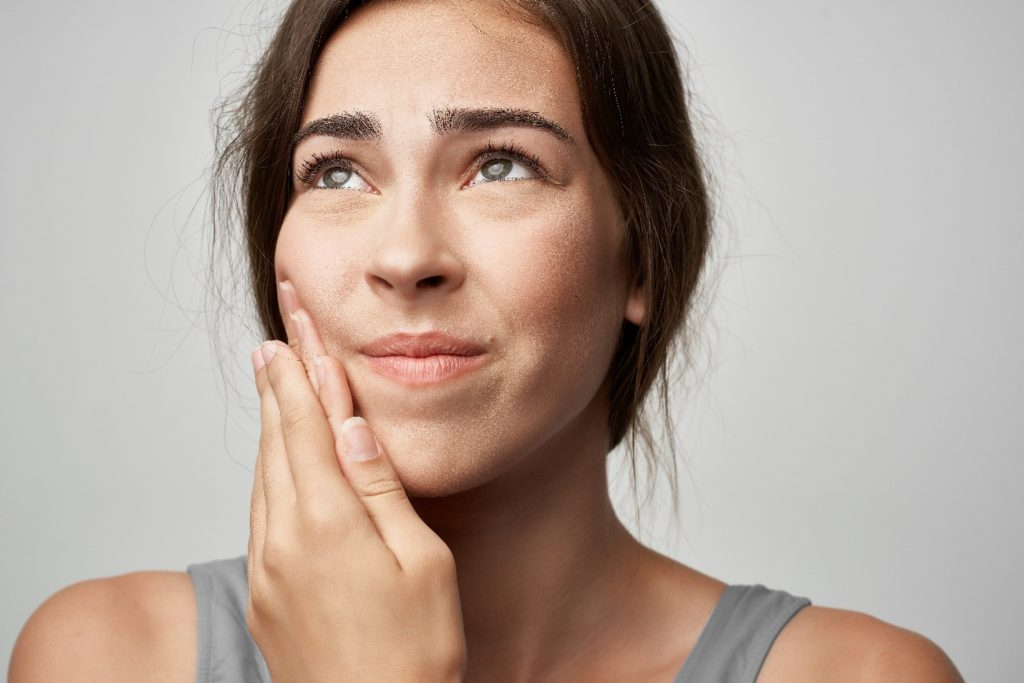 Woman experiencing soreness from Invisalign aligners